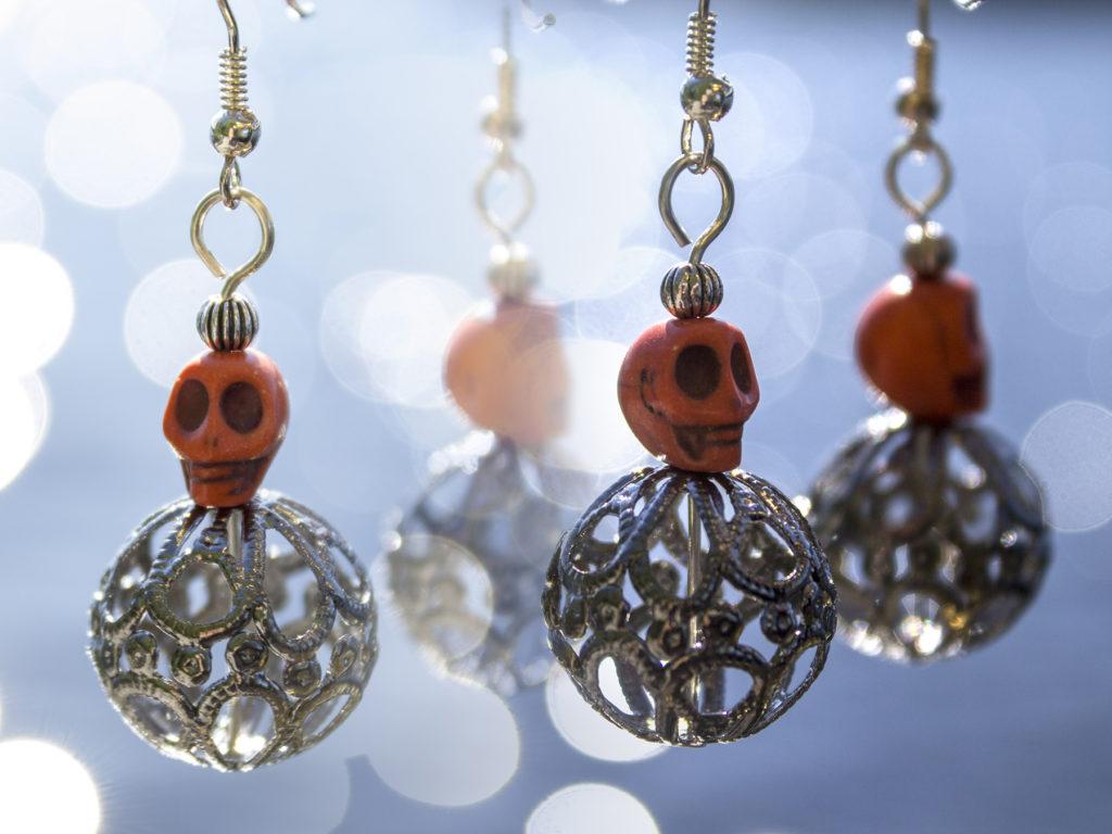Korvakorut, joissa on hopeapitsihelmet ja oranssit pääkallot.